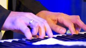 Manos masculinas del primer que juegan en el piano eléctrico rodeado centellando luces coloridas metrajes