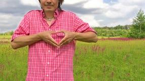 Manos masculinas en la dimensión de una variable del corazón en una naturaleza Foto de archivo libre de regalías