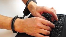 Manos masculinas en las esposas que mecanografían en el ordenador portátil, prevención de la delincuencia, ataque del pirata info almacen de video