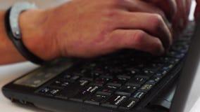 Manos masculinas en las esposas que mecanografían en el ordenador portátil, prevención de la delincuencia, ataque del pirata info almacen de metraje de vídeo
