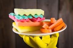 Manos masculinas en los guantes del yelliw que sostienen una hamburguesa hecha de diversos colores de las esponjas Concepto de co Imagen de archivo