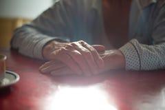 Manos masculinas mayores en la tabla Fotos de archivo