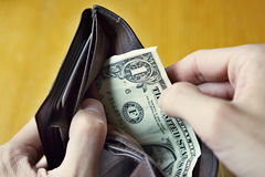 Manos masculinas que abren una cartera de cuero casi vacía con solamente un dólar americano (un USD, el dólar de EE. UU.) como sí Imagenes de archivo