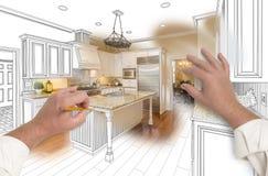 Manos masculinas que bosquejan la cocina de encargo con la foto que muestra a través imagen de archivo