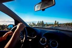 Manos masculinas que conducen el coche en el camino de la montaña Fotografía de archivo