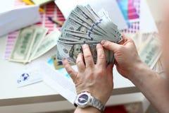 Manos masculinas que cuentan el dinero del paquete enorme imagen de archivo