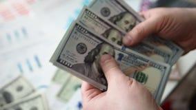 Manos masculinas que cuentan el paquete enorme de dólares americanos metrajes