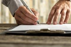 Manos masculinas que firman el formulario del documento, del contrato o de inscripción Fotos de archivo