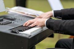 Manos masculinas que juegan el piano eléctrico fotografía de archivo