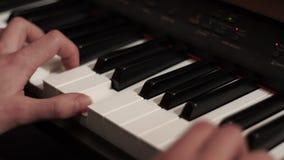 Manos masculinas que juegan el piano Juego del piano de la música Instrumento del teclado almacen de video