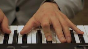 Manos masculinas que juegan el piano metrajes