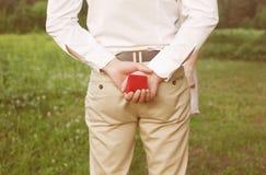 Manos masculinas que llevan a cabo el anillo en caja roja Foto de archivo