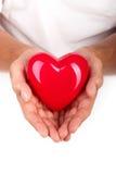 Manos masculinas que llevan a cabo el corazón rojo Imagenes de archivo