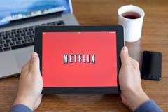 Manos masculinas que llevan a cabo el iPad con app Netflix en la pantalla en de
