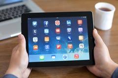 Manos masculinas que llevan a cabo el iPad con los medios sociales app en la pantalla en t imágenes de archivo libres de regalías