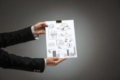 Manos masculinas que llevan a cabo el plan empresarial Foto de archivo