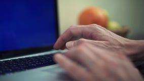 Manos masculinas que mecanografían el mensaje en los teclados del ordenador portátil con la pantalla verde almacen de video