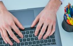 Manos masculinas que mecanografían en el teclado del ordenador portátil Hombre joven que usa el ordenador portátil concepto de tr Fotos de archivo