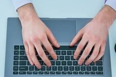 Manos masculinas que mecanografían en el teclado del ordenador portátil Hombre joven que usa el ordenador portátil concepto de tr Imagen de archivo libre de regalías