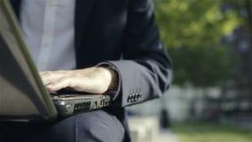 Manos masculinas que mecanografían en un teclado del ordenador portátil, al aire libre metrajes