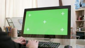 Manos masculinas que mecanografían un texto en un ordenador con la pantalla verde encendido almacen de metraje de vídeo