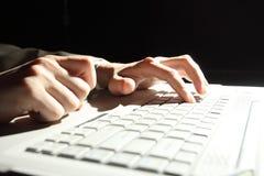Manos masculinas que pulsan en la computadora portátil Foto de archivo libre de regalías