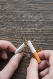 Manos masculinas que rompen un cigarrillo Imagen de archivo libre de regalías
