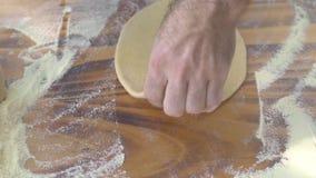 Manos masculinas que ruedan la pasta redonda con el perno de rodillo para la empanada que cuece en la tabla de madera Manos del c almacen de video