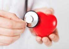 Manos masculinas que sostienen el corazón y el estetoscopio rojos Foto de archivo