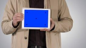 Manos masculinas que sostienen la tableta con la maqueta de la pantalla azul en fondo de la pendiente fotografía de archivo