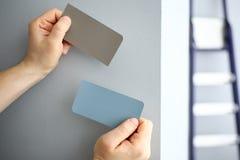 Manos masculinas que sostienen las muestras de papel de nuevo color de la pared imagen de archivo