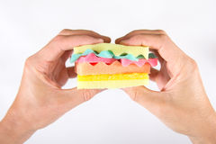 Manos masculinas que sostienen una hamburguesa hecha de diversos colores de las esponjas Concepto de comida malsana y de producto Imágenes de archivo libres de regalías