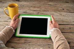 Manos masculinas que sostienen una tableta con una pantalla en blanco en el primer de madera de la tabla Foto de archivo