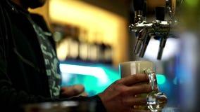 Manos masculinas que vierten la cerveza en la taza de cristal del golpecito en pub almacen de metraje de vídeo