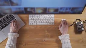 Manos masculinas usando el ordenador portátil y el ratón para buscar imágenes en la pantalla de ordenador almacen de video