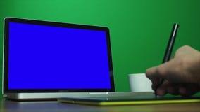 Manos masculinas usando una tableta digital del dibujo y un ordenador portátil Llave de la croma en el fondo