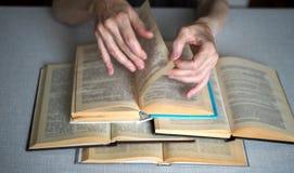 Manos mayores con los libros abiertos, cierre de la persona para arriba, foco seleccionado, falta de definición imágenes de archivo libres de regalías