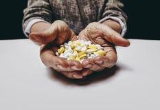 Manos mayores de la mujer con las píldoras Imágenes de archivo libres de regalías