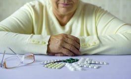 Manos mayores de la mujer con las píldoras y lentes en el primer de la tabla en casa foto de archivo libre de regalías