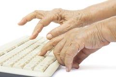 Manos mayores de la mujer en el teclado de ordenador Imágenes de archivo libres de regalías