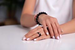 Manos modelo con la manicura, clavos blancos, anillo negro del primer con la piedra, pulsera hecha de las gotas negras brillantes fotos de archivo libres de regalías