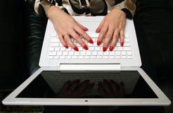 Manos mujeriles en una computadora portátil blanca. imagenes de archivo
