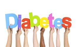 Manos Multi-étnicas que llevan a cabo la diabetes de la palabra Fotografía de archivo