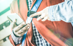 Manos multirraciales de los pares que se divierten con los teléfonos elegantes móviles Imagen de archivo libre de regalías