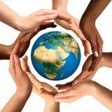 Manos multirraciales que rodean el globo de la tierra Foto de archivo libre de regalías