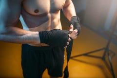 Manos musculares de la persona masculina en vendajes negros Foto de archivo libre de regalías