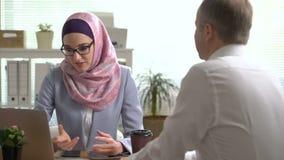 Manos musulmanes jovenes de la sacudida de la mujer de negocios con un hombre caucásico durante una reunión en oficina almacen de video