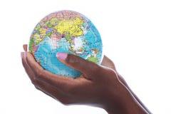 Manos negras que sostienen un globo del mundo aislado Imágenes de archivo libres de regalías