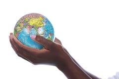 Manos negras que sostienen un globo del mundo aislado Foto de archivo