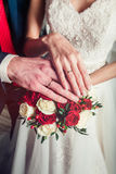 Manos novia y novio con los anillos en el primer del ramo Imagen de archivo